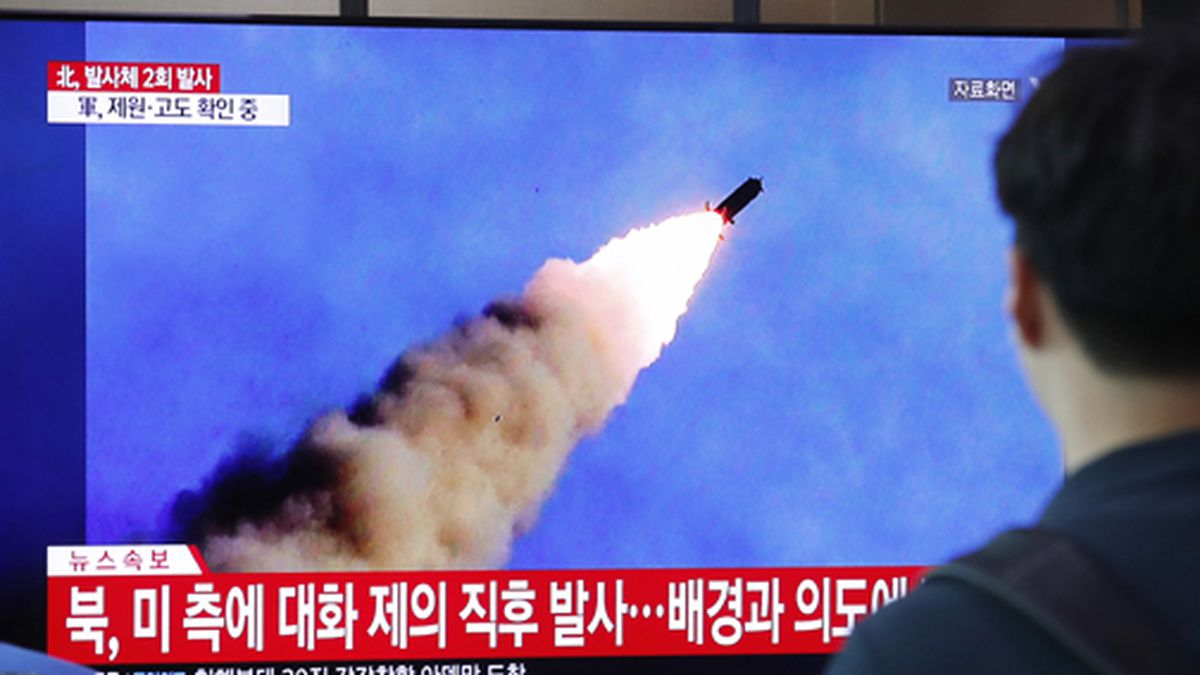 People watch a TV showing a file image of a North Korea's missile launch during a news program...