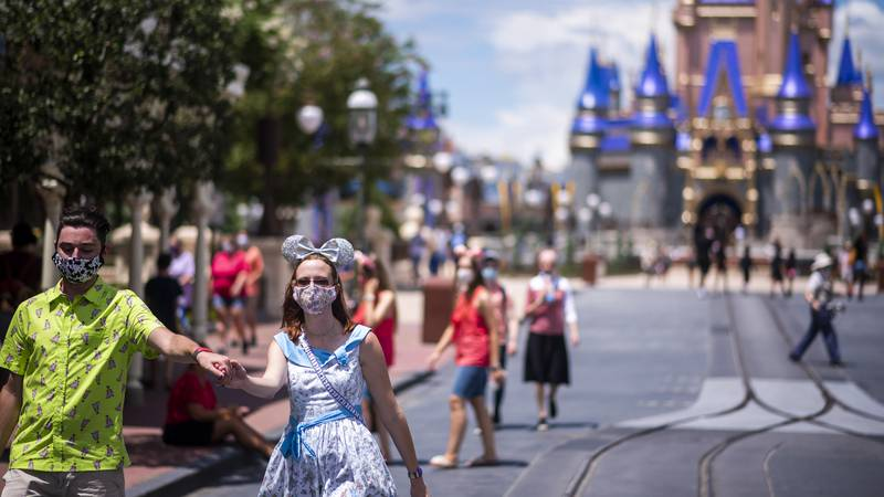 Guests wear required face masks due to the Covid-19 pandemic on Main Street, U.S.A. in front of...