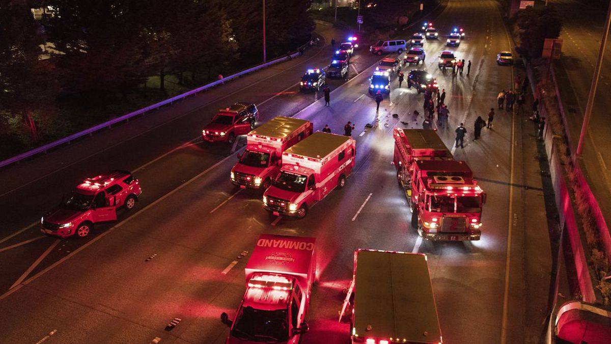 Emergency personnel work at the site where a driver sped through a protest-related closure on the Interstate 5 freeway in Seattle, authorities said early Saturday, July 4, 2020. (Source: James Anderson via AP)