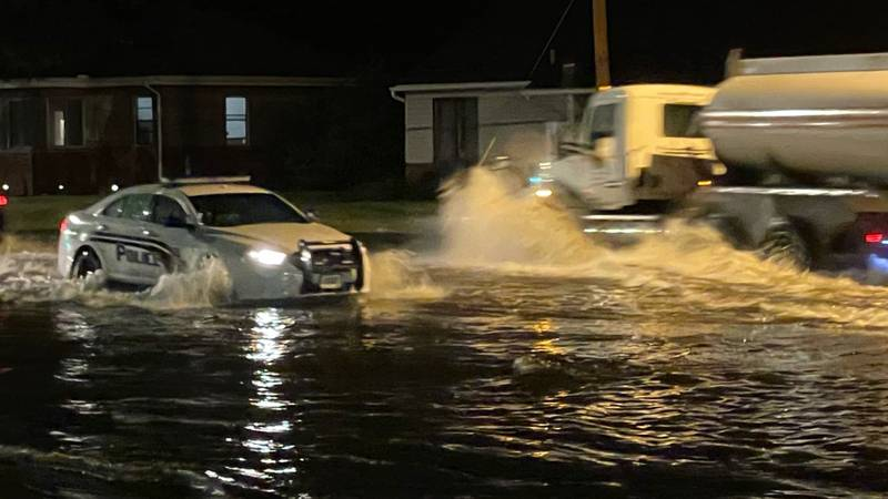 A Toledo Police squad car drives through high water on Douglas Rd. after heavy rainfall from a...