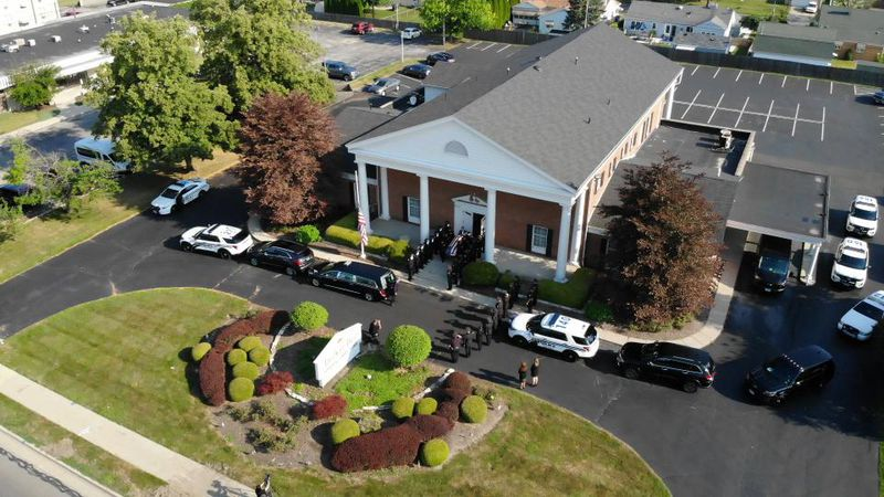 The hearse carrying Toledo Police Officer Anthony Dia prepares to leave the funeral home...