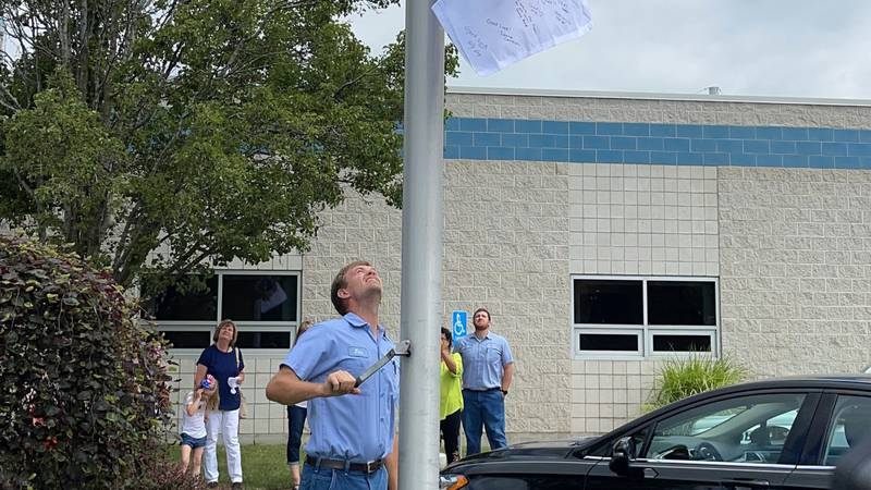 Two-time Olympian, Jacob Wukie raises the Olympic flag.