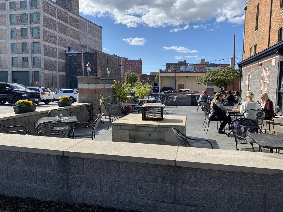 Customers sit outside and enjoy dinner at Ye Olde Durty Bird in downtown Toledo even with...