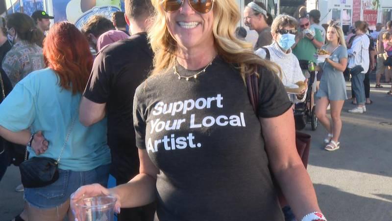 """A woman wears a """"Support Local Artist"""" T-shirt."""