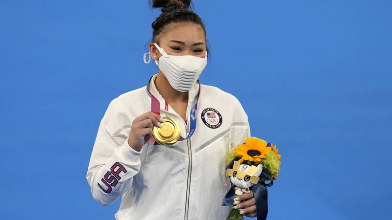 Sunisa Lee of the Unites States displays her gold medal for the artistic gymnastics women's...