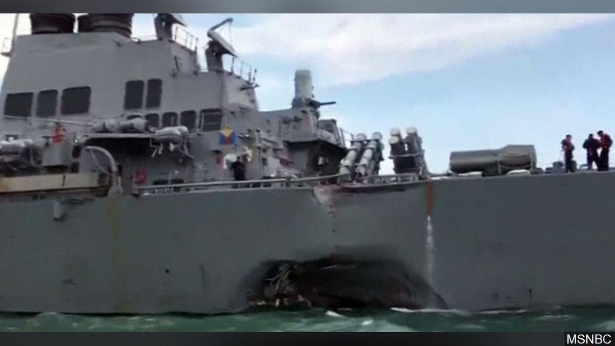 U.S. Navy Guided Missile Destroyer USS John S. McCain with a hole in its rear left side, in...