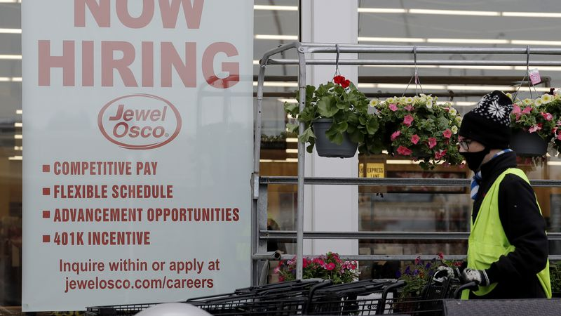 A man pushes carts as a hiring sign shows at a Jewel Osco grocery store in Deerfield, Ill.,...