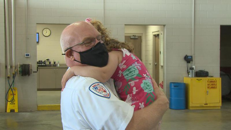 Chief Tuckey hugs his granddaughter during a visit at the Tecumseh Fire Station.