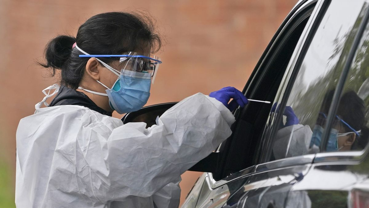 A medical worker prepares to administer a COVID-19 swab at a drive-through testing site in...