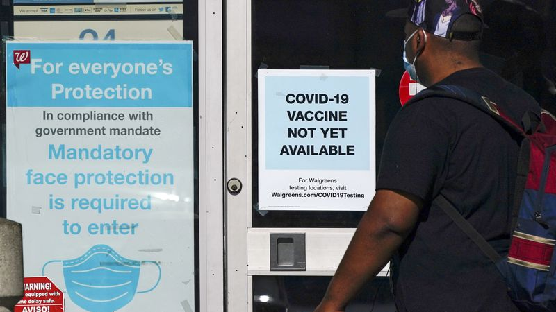 FILE - In this Dec. 2, 2020, file photo, a customer walks past a sign indicating that a...