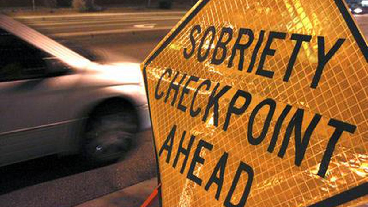 FILE - In this Dec. 29, 2011 file photo, a car approaches a sobriety checkpoint set up along a...