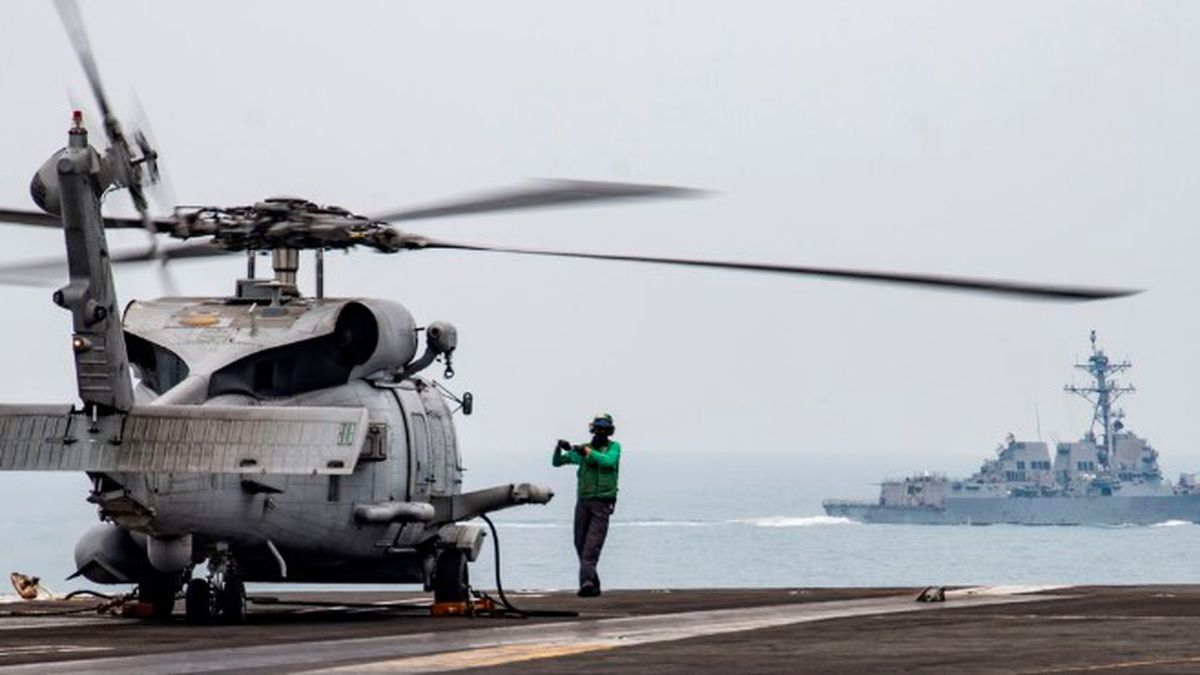 In this photo provided by the U.S. Navy, Aviation Electronics Technician 3rd Class James Benzel, from Louisville, Ohio, assigned to the Saberhawks of Helicopter Maritime Strike Squadron, signals an MH-60R Sea Hawk to disengage its rotors on the flight deck of the USS Ronald Reagan (CVN 76) as USS Mustin (DDG 89) steams alongside in the South China Sea, Thursday, July 9, 2020. (Source: Mass Communication Specialist 3rd Class Erica Bechard/U.S.Navy via AP)
