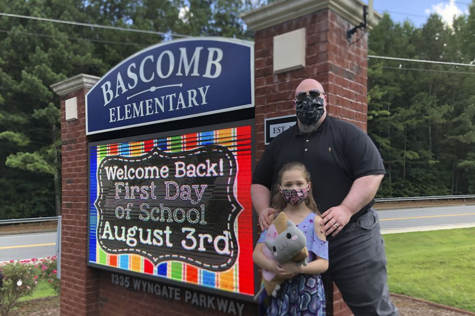 John Barrett and his daughter Autumn pose for photos outside Bascomb Elementary School in Woodstock, Ga., Thursday, July 23, 2020. Barrett says he will educate his daughter virtually and keep her out of in-person classes in Cherokee County schools, even though he's worried she will fall behind on her special education plans, because of concerns about COVID-19's spread. Cherokee County, near Atlanta, is one of many districts nationwide that gave parents a choice between in-person and all-online classes this fall.