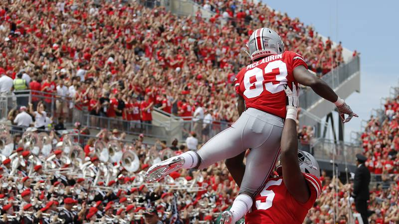 Ohio State receiver Terry McLaurin is lifted in celebration by teammate Jaylen Harris after...