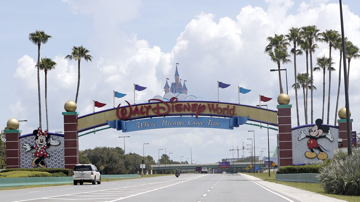 FILE - In this Thursday, July 2, 2020, file photo, cars drive under a sign greeting visitors...