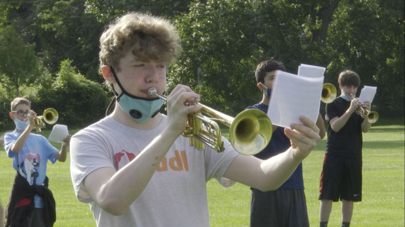 Students are wearing masks when they're not playing, rehearse in groups and are extra spread...