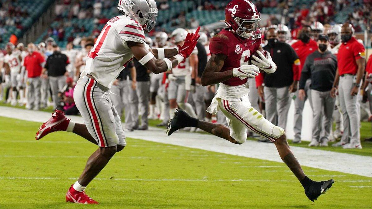 Alabama wide receiver DeVonta Smith scores a touchdown past Ohio State safety Josh Proctor...