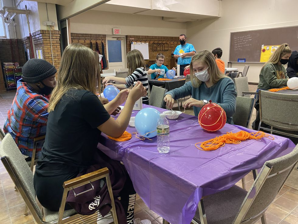 SYML mentor, Rachel Simpson works side by side students offering guidance on the groups current craft activity.